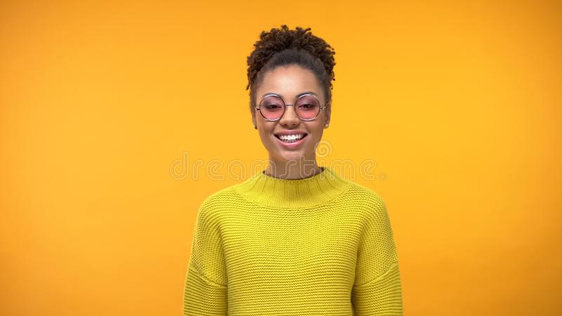 Donna graziosa sorridente in occhiali rosa e maglione giallo, positività della gioventù fotografie stock libere da diritti