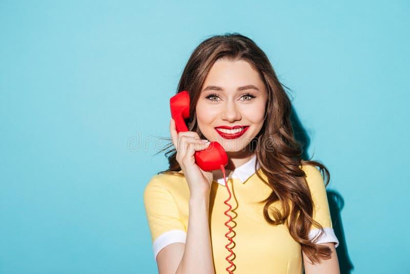 Donna graziosa sorridente in vestito che tiene il retro tubo del telefono fotografie stock libere da diritti