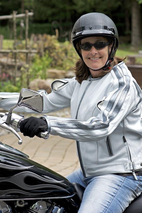 Donna graziosa su un motociclo fotografia stock