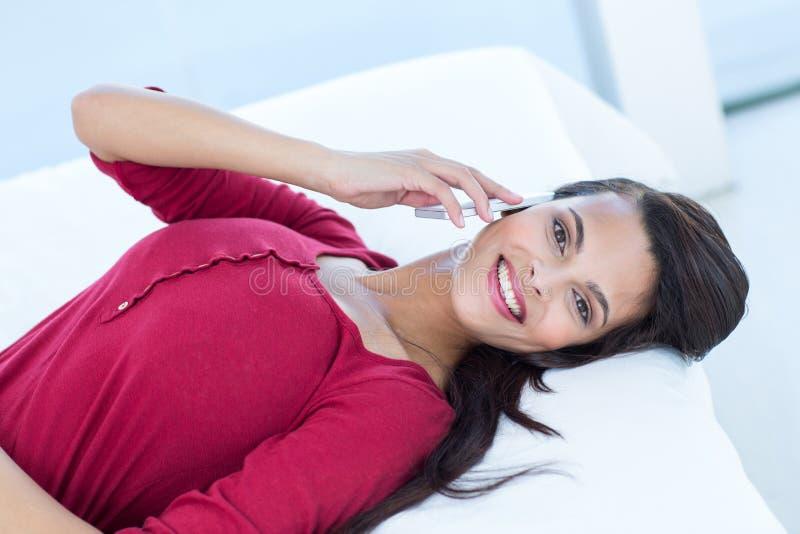 Donna graziosa sul telefono che si trova sul suo letto fotografia stock libera da diritti