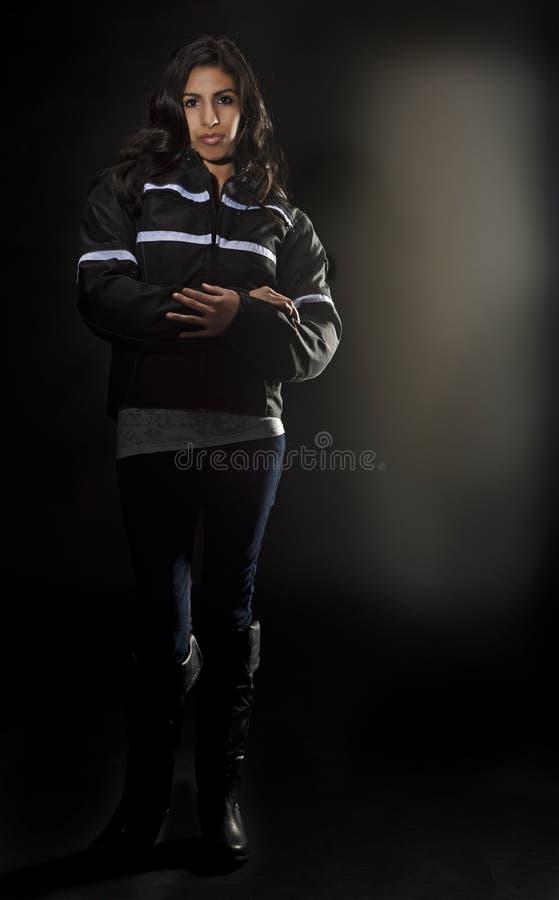 Donna graziosa in suo ingranaggio nero di guida immagine stock
