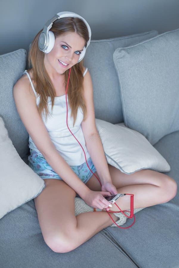 Donna graziosa sveglia che ascolta la sua musica fotografie stock libere da diritti