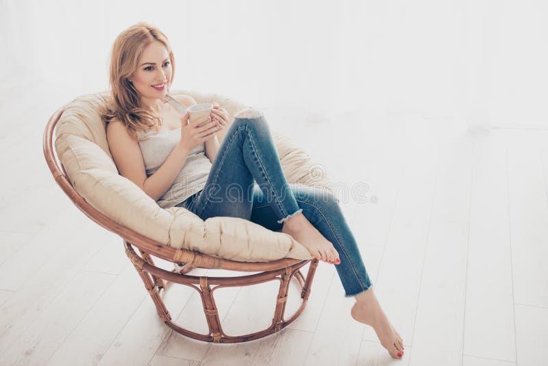 Donna graziosa sveglia felice che si siede nella poltrona nel fine settimana w fotografia stock libera da diritti
