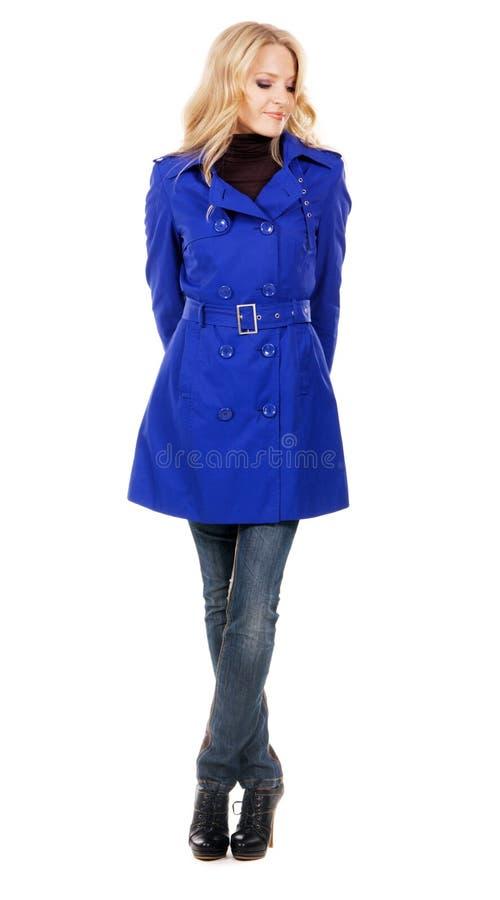 Donna graziosa in un cappotto blu immagini stock