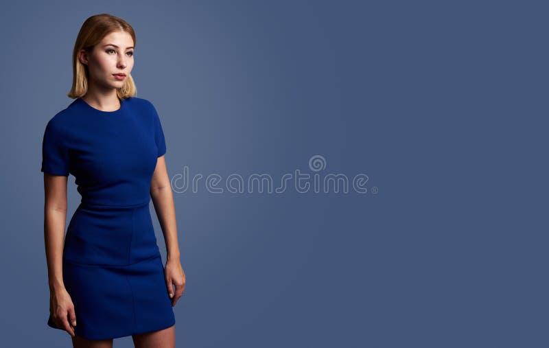 Donna graziosa in un distogliere lo sguardo blu del vestito fotografia stock libera da diritti
