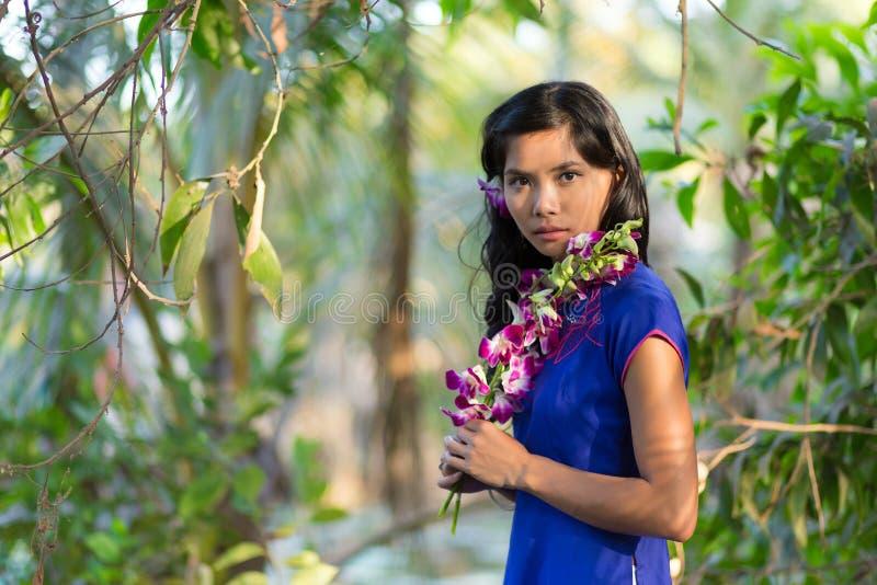 Donna graziosa in vestito blu che tiene fiore porpora fotografia stock libera da diritti