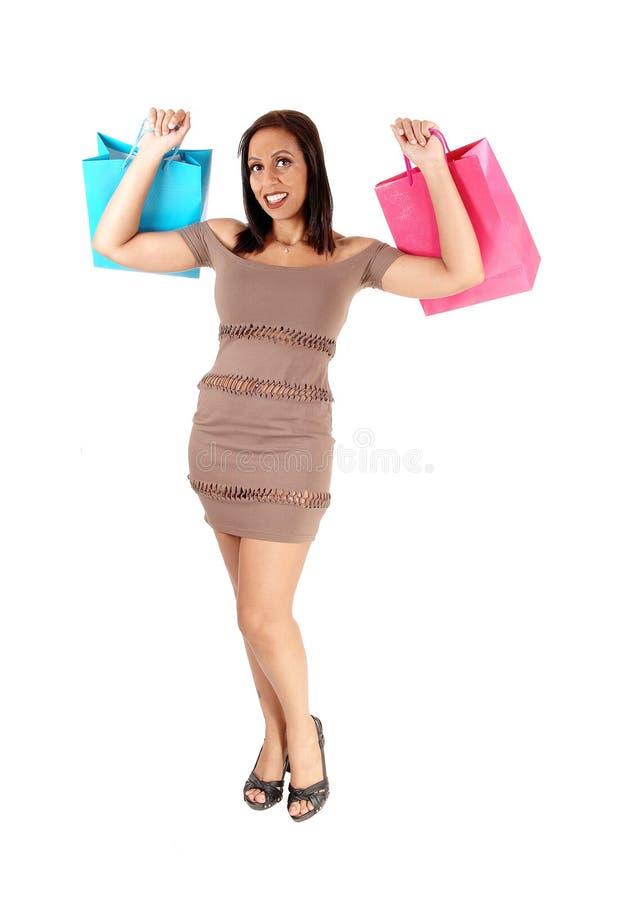 Donna graziosa in vestito che tiene i suoi sacchetti della spesa immagine stock