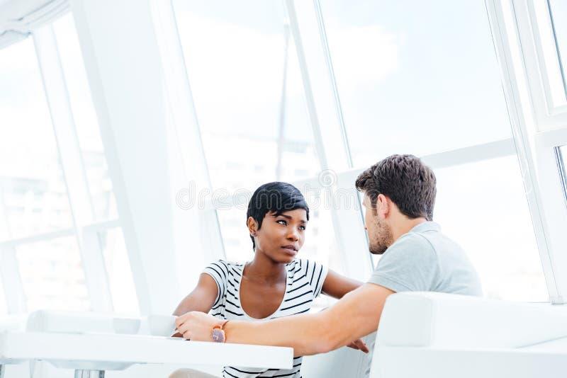 Donna graziosa in vetri che si siedono e che parlano con il suo ragazzo fotografia stock libera da diritti