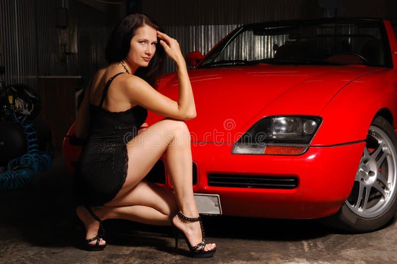 Donna graziosa vicino all'automobile rossa fotografie stock