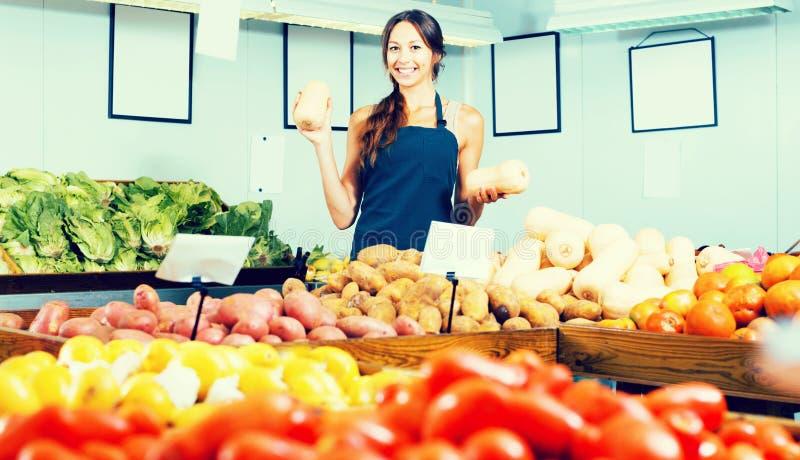 Donna in grembiule che vende le piccole zucche decorative immagine stock libera da diritti