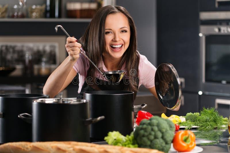 Donna in grembiule sulla cucina moderna fotografia stock libera da diritti