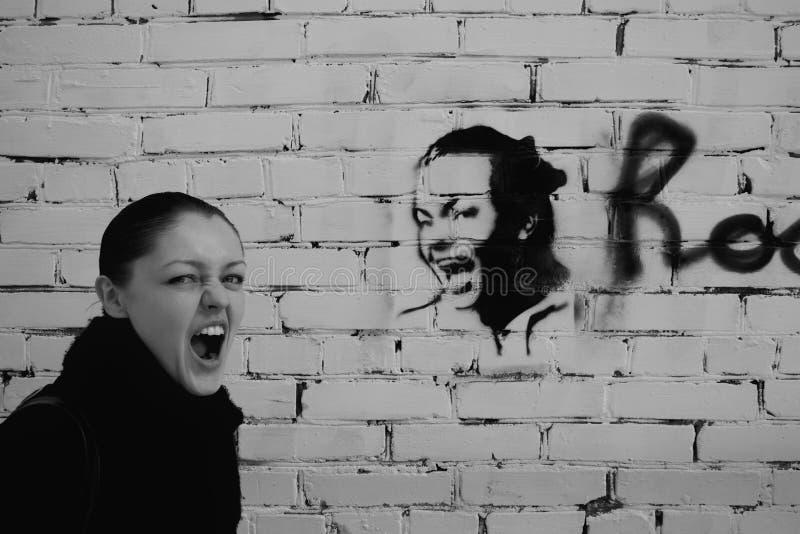 Donna gridante su un muro di mattoni fotografie stock libere da diritti