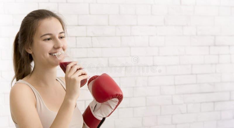 Donna in guanto di boxe che beve un frullato rosso di detox sulla parete di mattoni bianchi immagine stock