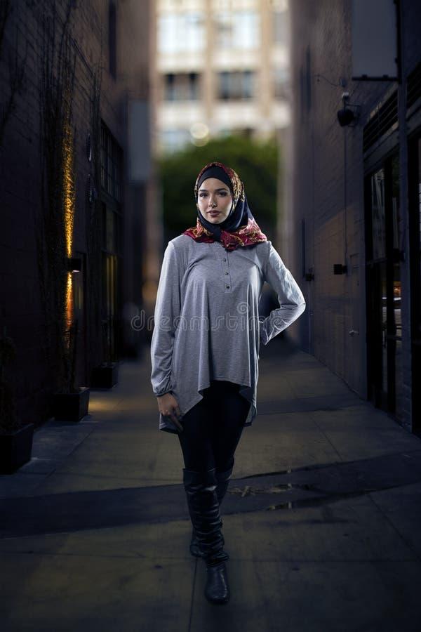 Donna in Hijab che cammina nella città fotografia stock