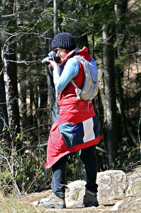 Donna Hikier che prende foto fotografia stock libera da diritti