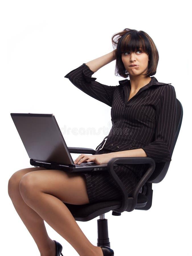 Donna imbarazzata del brunette nella seduta scura del vestito immagine stock