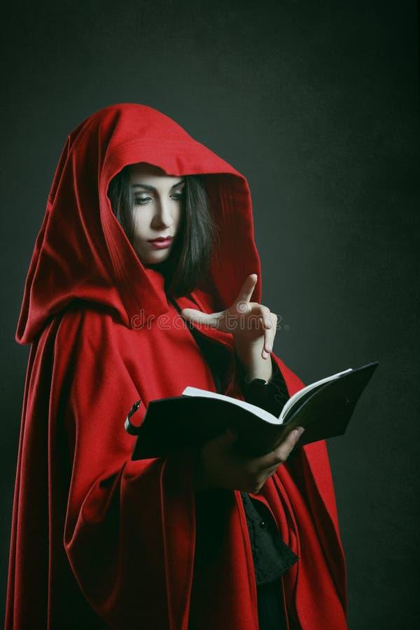 Donna incappucciata rossa che legge un libro fotografie stock libere da diritti