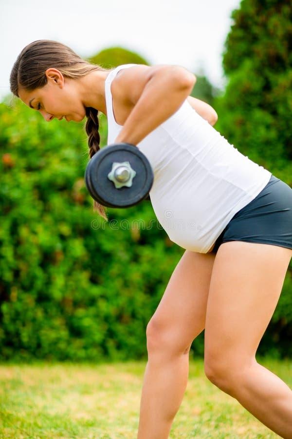 Donna incinta adatta che si esercita con le teste di legno in parco fotografie stock libere da diritti