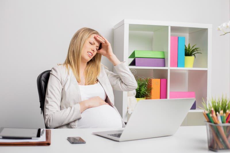 Donna incinta all'ufficio che ha emicrania fotografie stock