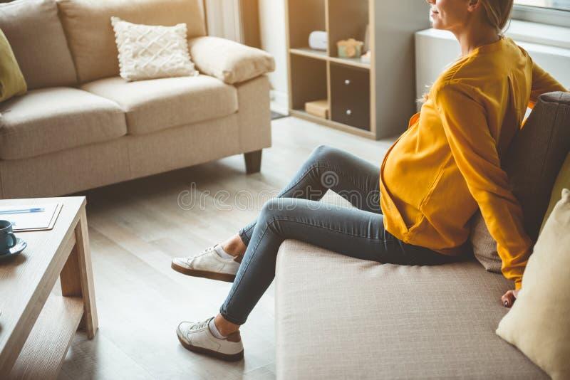 Donna incinta allegra che riposa sullo strato a casa immagine stock