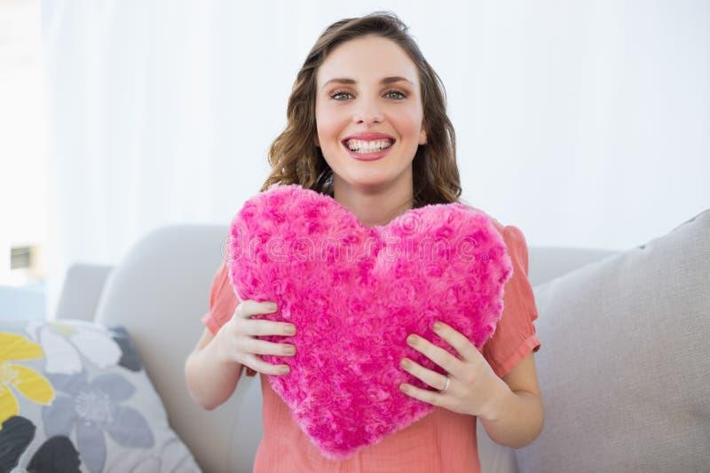 Donna incinta allegra che tiene il cuscino rosa del cuore che si siede sullo strato immagine stock libera da diritti