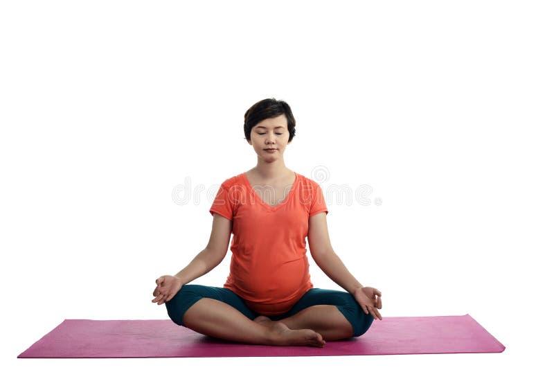 Donna incinta asiatica che fa yoga immagine stock