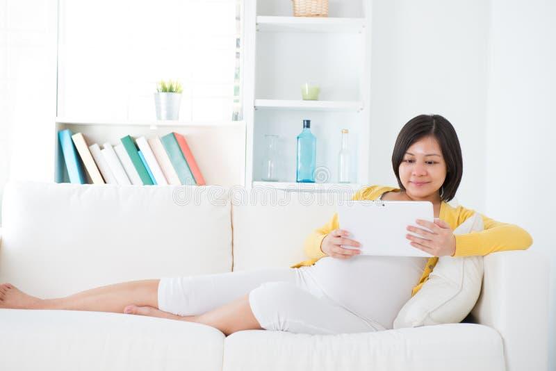 Donna incinta asiatica che per mezzo del computer della compressa fotografie stock libere da diritti
