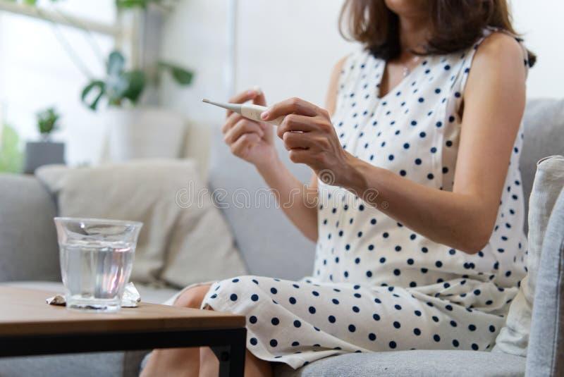 Donna incinta asiatica che si siede sul termometro della tenuta del sof? sulla mano sinistra e che fora medicina sulla mano destr fotografia stock
