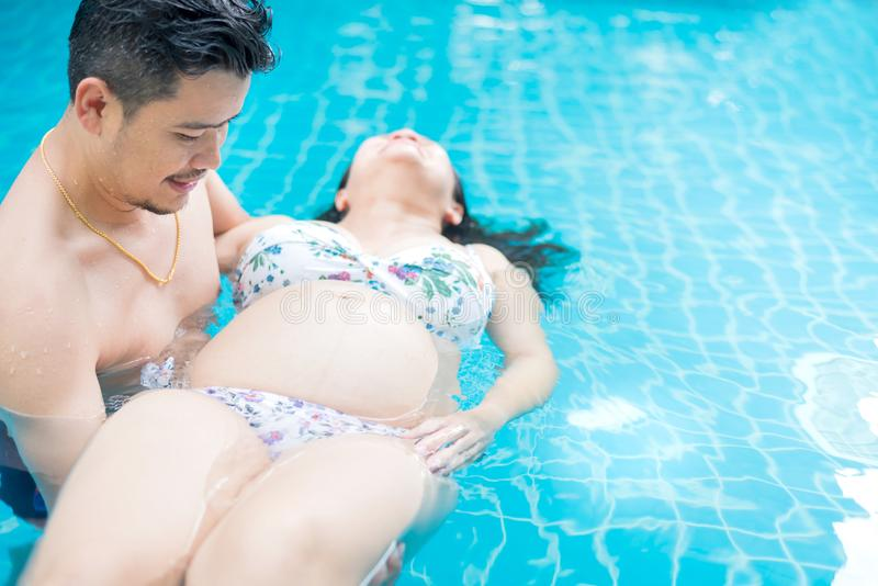 Donna incinta asiatica con la grande pancia Rilassi ed eserciti alla piscina fotografia stock