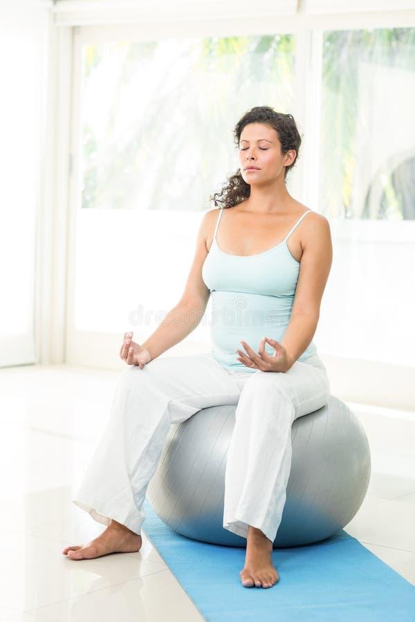 Donna incinta bionda pacifica che si siede sulla palla di esercizio fotografia stock libera da diritti