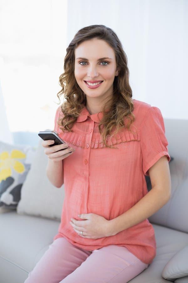 Donna incinta calma contenta che tiene il suo smartphone che si siede sullo strato immagini stock