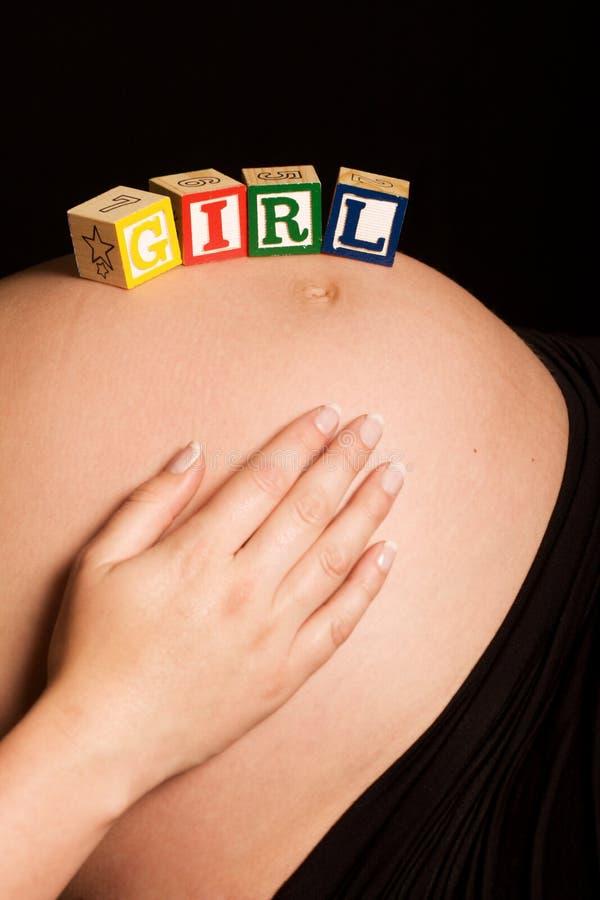 Donna incinta caucasica con i blocchi di legno fotografia stock