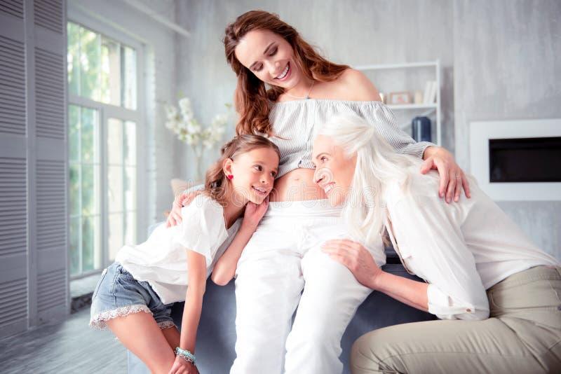 Donna incinta che abbraccia madre e figlia che ascoltano la sua pancia fotografie stock libere da diritti