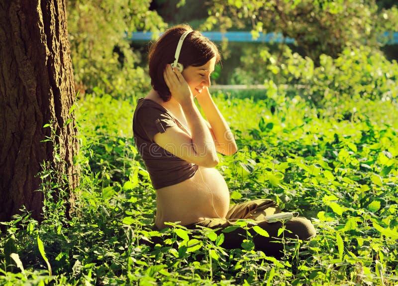 Donna incinta che ascolta una musica al parco. fotografie stock libere da diritti