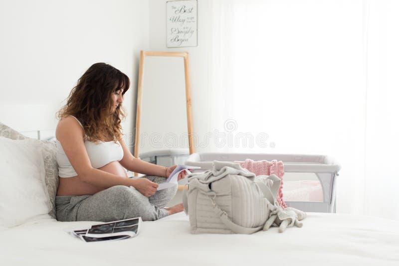Donna incinta che controlla l'ultimo ultrasuono fotografia stock libera da diritti