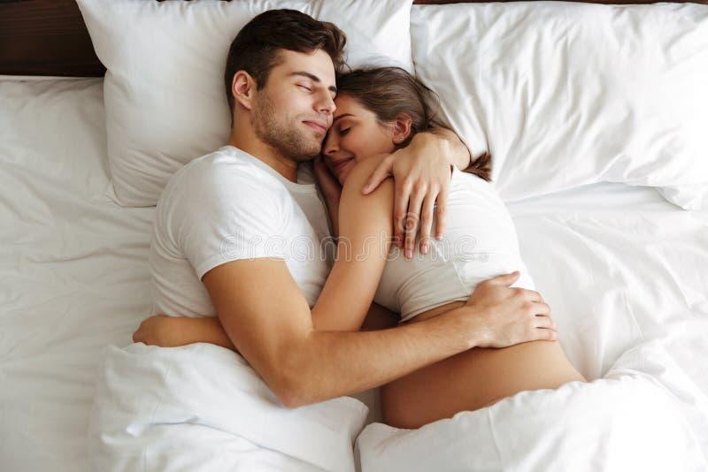 Donna incinta che dorme a letto con il suo marito fotografia stock