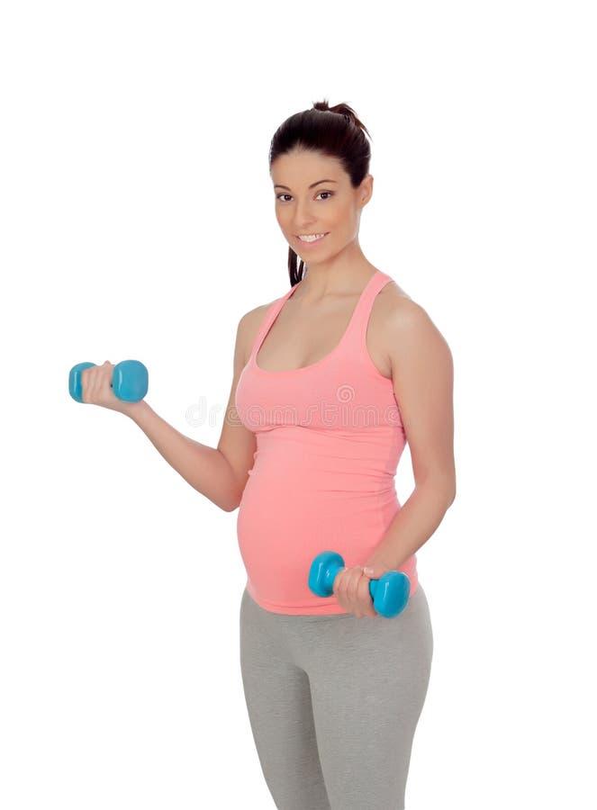 Donna incinta che fa esercizio con le teste di legno immagini stock libere da diritti