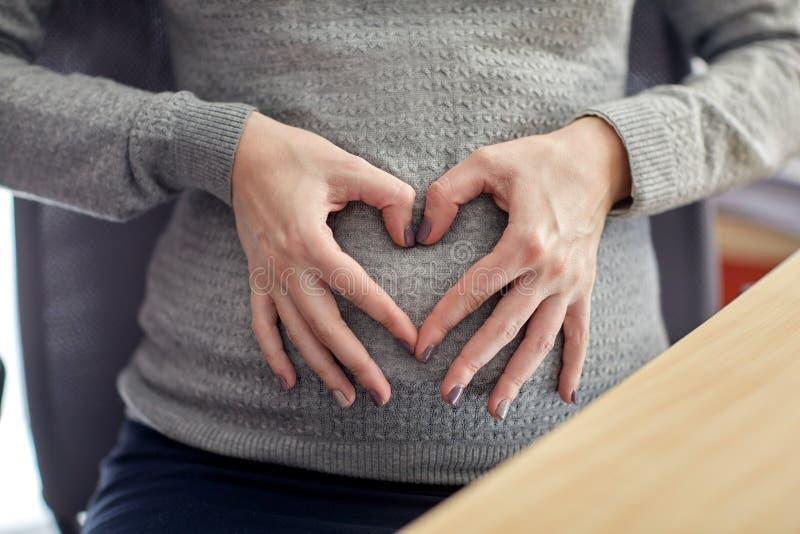Donna incinta che fa forma del cuore all'ufficio fotografia stock