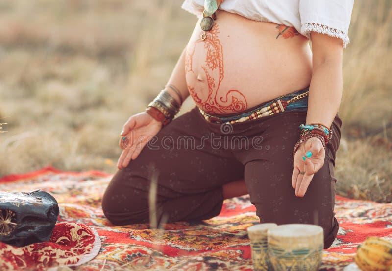 Donna incinta che fa yoga nel campo al tramonto fotografia stock libera da diritti