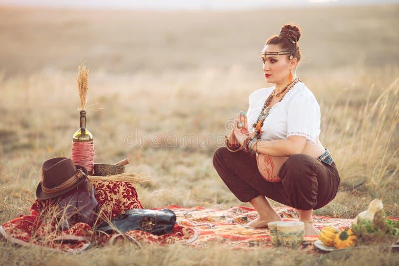 Donna incinta che fa yoga nel campo al tramonto immagini stock