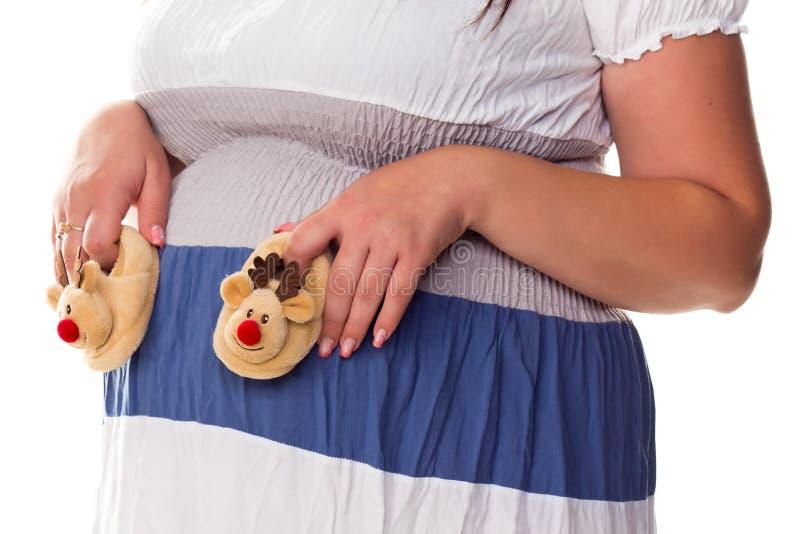 Donna incinta che fora i bootees del bambino alla sua pancia fotografia stock
