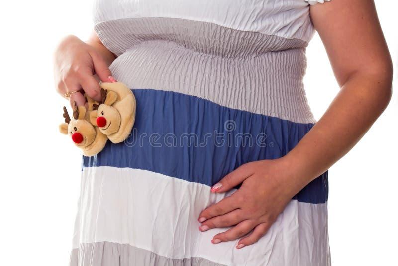 Donna incinta che fora i bootees del bambino alla sua pancia fotografie stock