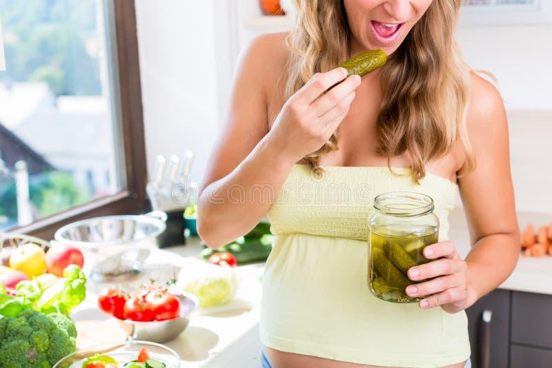 Donna incinta che ha bisogno per i cetriolini marinati immagini stock libere da diritti