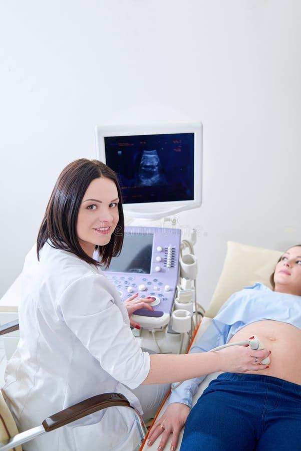Donna incinta che ha esame con gli ultrasuoni alla clinica immagine stock