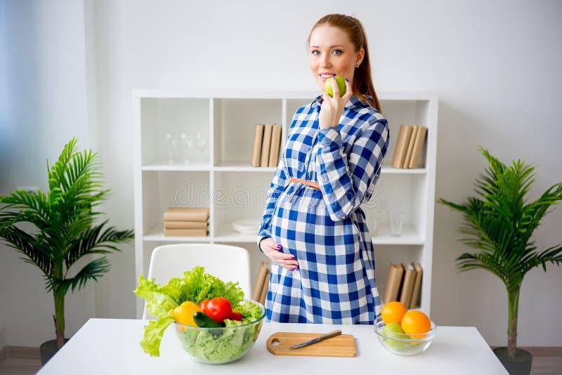 Donna incinta che mangia frutta fotografie stock