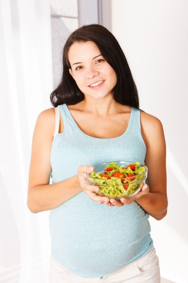 Donna incinta che mangia sorridere dell'insalata fotografia stock