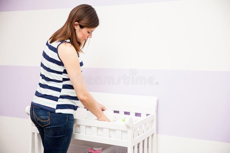 Donna incinta che organizza la scuola materna fotografie stock