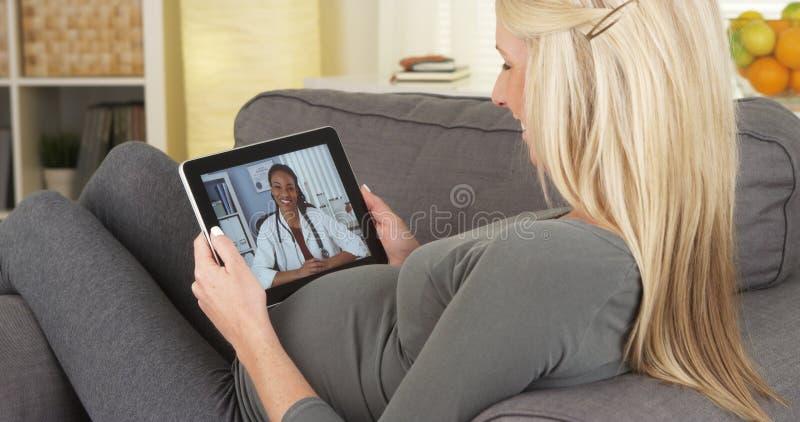 Donna incinta che parla con medico sulla compressa immagini stock