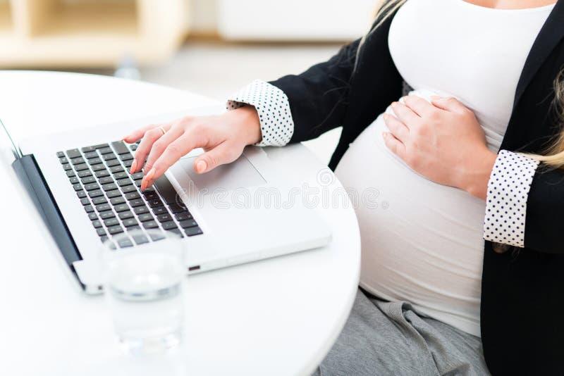 Donna incinta che per mezzo del computer portatile immagini stock