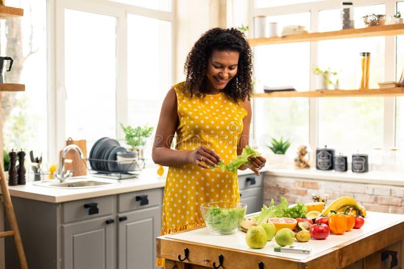 Donna incinta che produce insalata nella sua cucina immagine stock libera da diritti